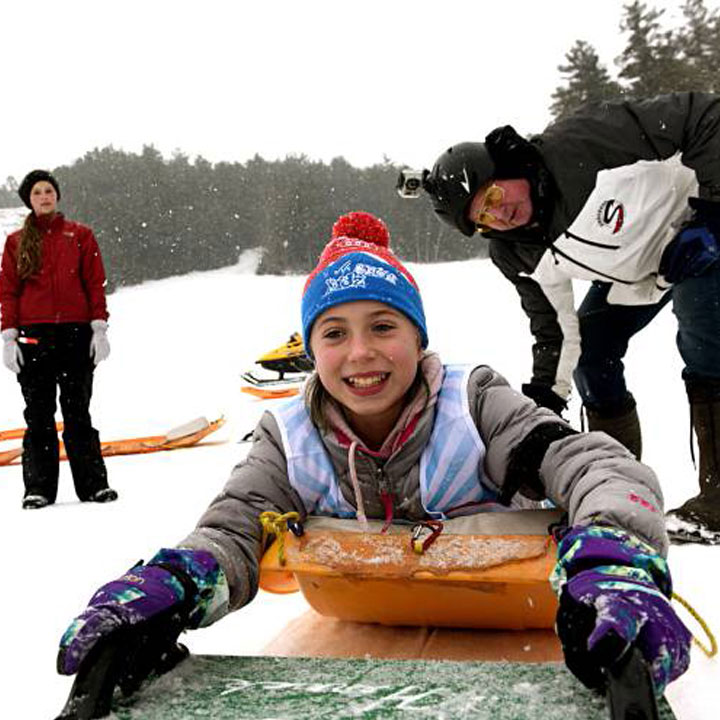 Young girl on toboggan with two other adults at Arrowhead Recreation Area